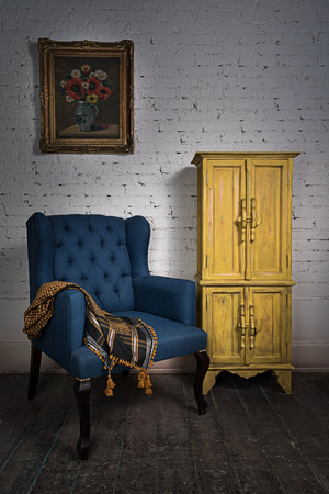 Composition of vintage blue armchair, yellow cupboard and framed painting Stock Photo - 55490724