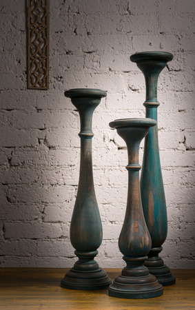 gunmetal: Composition of three blue gray vintage wooden candlesticks on a background of wooden floor and white painted brick wall