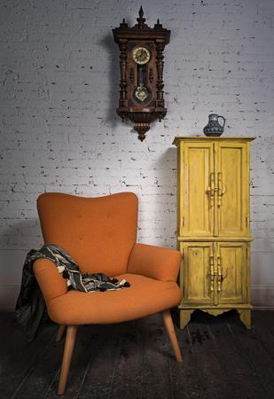 reloj de pendulo: Composici�n del vintage sill�n naranja, amarillo armario, reloj de p�ndulo y un pa�uelo negro