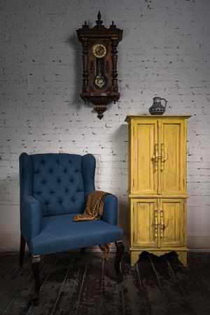 reloj de pendulo: Todavía vida del sillón de la vendimia azul, amarillo armario, reloj de péndulo y una bufanda de color naranja adornado en el estudio