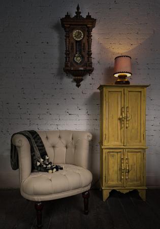 reloj de pendulo: Todav�a vida del vintage sill�n beige, amarillo armario, reloj de p�ndulo de madera y l�mpara de mesa iluminada en un piso de madera y ladrillos blancos de la pared