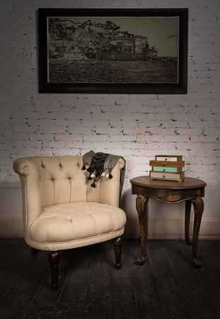 antique table: Vintage still life of old beige armchair, small drawers unit, hanged framed painting and one small antique table on dark brown wooden floor and white bricks wall in Studio