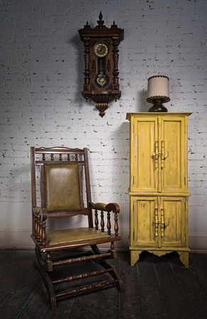 reloj de pendulo: Composición de retro madera mecedora, armario empotrado de color amarillo y el reloj de péndulo en la sala de estar Foto de archivo