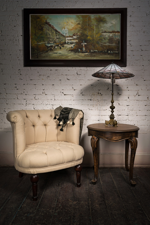 antique table: Vintage still life of retro beige armchair, table lamp on antique table and hanged framed painting on dark brown wooden floor and white bricks wall in studio