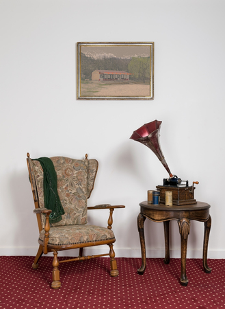 phonograph: Retro ornate armchair, a 1911 old phonograph with three cylinder records on round coffee table and hanged painting on red carpet