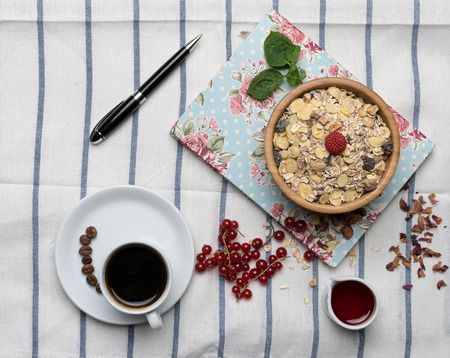 block note: Healthy breakfast with muesli, raspberry, cherries and coffee on a background of white tablecloth, block note, and black pen