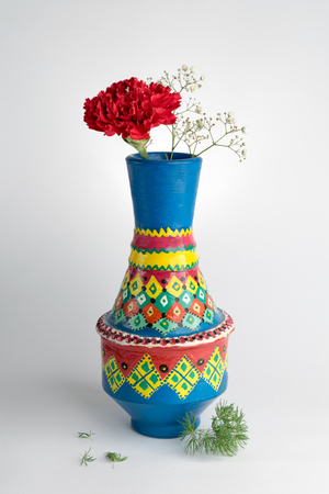colorful still life: Still life composition of colorful pottery vase with a red flower on white background Stock Photo