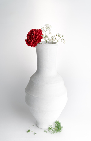 Still life composition of white pottery vase and red flower on white background Banque d'images