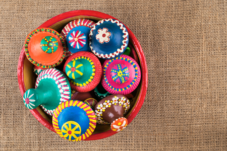lids: Still life shot showing top view of pottery lids stacked in a pottery bowl on sackcloth background Stock Photo