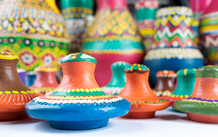 lids: Still life of colorful pottery lids on blurred background of colored pottery vases