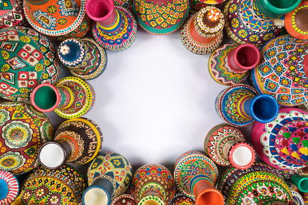 compacted: Top view showing a composition of artistic painted handcrafted pottery vases compacted around an empty circle on white background Stock Photo