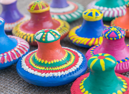 angled view: Angled view showing a still life of colorful painted pottery lids on sackcloth background Stock Photo