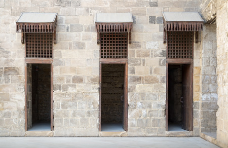 adjacent: Three adjacent opened doors in a stone wall at the main courtyard of an old mosque in Old Cairo, Egypt