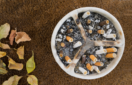 dead leaves: White pottery handmade ashtray full of a huge number of cigarettes and ashes on a background of sackcloth and dead leaves
