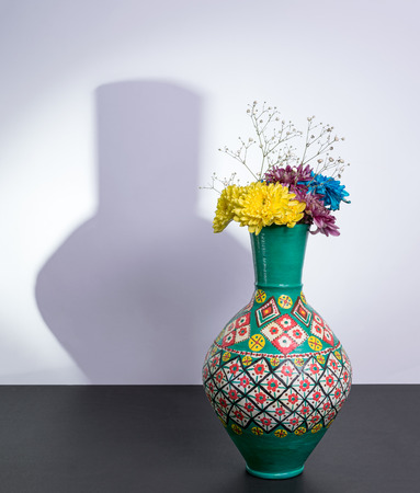 excluding: Colorful Egyptian traditional pottery vase, three yellow, blue and violet flowers with harsh shadow excluding flowers over black table and white wall Stock Photo