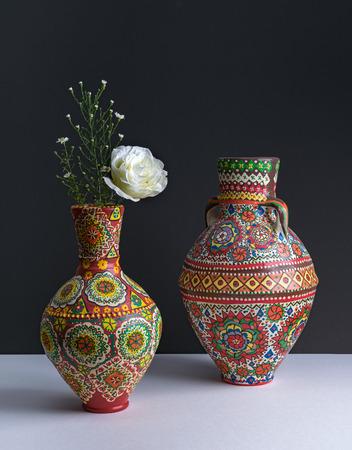 petites fleurs: Composition Nature morte de deux vases colorés de poterie, fleur blanche, et de petites fleurs sur fond de tableau blanc et mur sombre Banque d'images