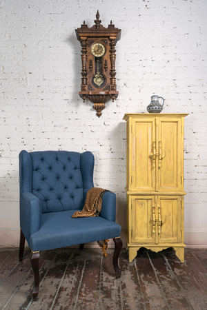 pendulum: Still life of vintage blue armchair, yellow cupboard, pendulum clock and orange ornate scarf in studio Stock Photo