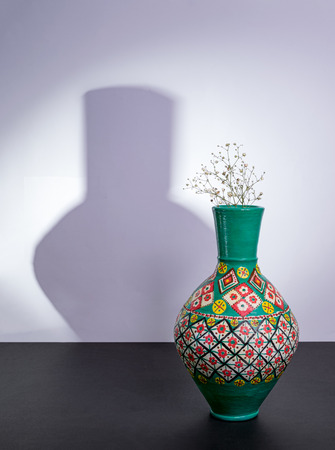Colorful Egyptian traditional pottery vase, small white flowers with harsh shadow excluding flowers shadow over black table and white wall