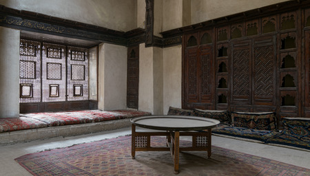 interleaved: One of the rooms of El Sehemy house, an old Ottoman era house in Cairo, originally built in 1648. The room have an interleaved wooden window (Mashrabiya) with built-in couch, and an embedded wooden cupboard
