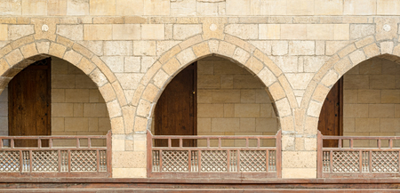 balustrades: Front view of three arches with interleaved wooden balustrades at the arcade surrounding the courtyard of caravanserai (Wikala) of al-Ghuri, Medieval Cairo, Egypt