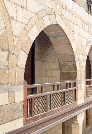 balustrades: Angled view of one arch with interleaved wooden balustrades at the arcade surrounding the courtyard of caravansery (Wikala) of al-Ghuri, Medieval Cairo, Egypt Stock Photo