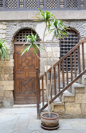 interleaved: View of the courtyard of Beit El Set Waseela (Waseela Hanem House), showing a wooden closed door and window with interleaved wooden grid and stair with wooden handrail leading to the upper floor, Medieval Cairo, Egypt