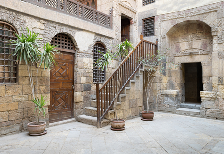 interleaved: View of the courtyard of Beit El Set Waseela (Waseela Hanem House), showing a wooden closed door and two windows with interleaved wooden grid and stair with wooden handrail leading to the upper floor, Medieval Cairo, Egypt