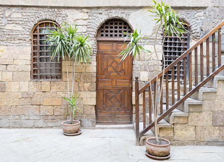 interleaved: Facade of Beit El Set Waseela (Waseela Hanem House), showing a wooden closed door and two window with interleaved wooden grid and stair with wooden handrail, Medieval Cairo, Egypt