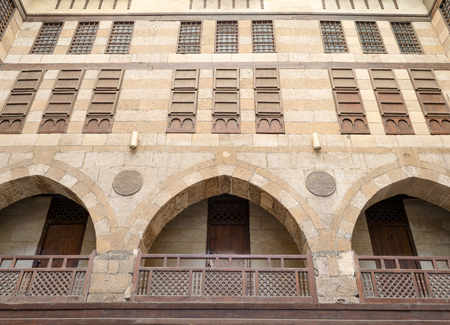 balustrades: Low angle view of the facade of caravansary (Wikala) of al-Ghuri with vaulted arcades, wooden balustrades, and windows covered by interleaved wooden grids (mashrabiyya), Medieval Cairo, Egypt