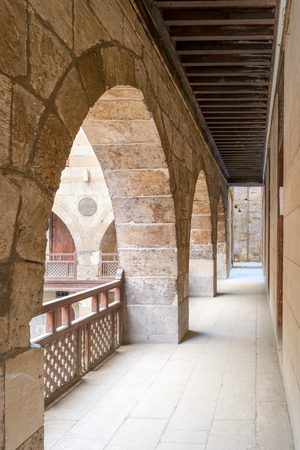 balustrades: Angled view of one arch with interleaved wooden balustrades at the arcade surrounding the courtyard of caravansary (Wikala) of al-Ghuri, Medieval Cairo, Egypt