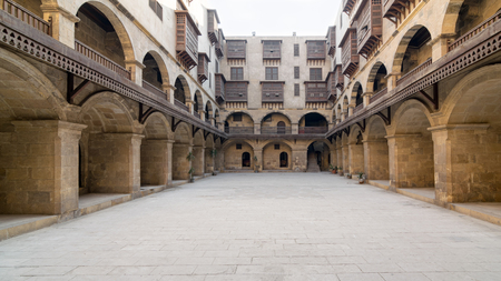 Facade of caravansary (Wikala) of Bazaraa, with vaulted arcades and windows covered by interleaved wooden grids (mashrabiyya), suited in Tombakshia street, Al Gamalia district, Medieval Cairo, Egypt Stock Photo