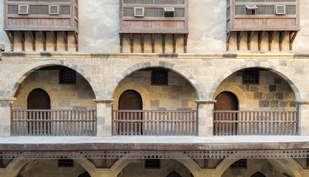 balustrades: Front view of three arches with interleaved wooden balustrades at the arcade surrounding the courtyard of caravansary (Wikala) of Bazaraa, Medieval Cairo, Egypt
