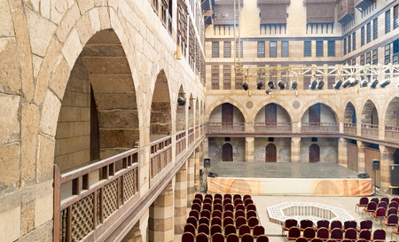 interleaved: Courtyard of caravanserai (Wikala) of al-Ghuri, surrounded by two floors of vaulted arcades leading to storages rooms, and three floors of windows covered by interleaved wooden grids (mashrabiyya), suited in Tablita Street parallel to al-Azhar Street, Med