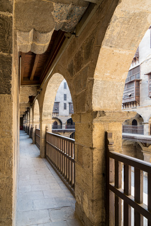 balustrades: Angled view of one arch with interleaved wooden balustrades at the arcade surrounding the courtyard of caravansary (Wikala) of Bazaraa, Medieval Cairo, Egypt