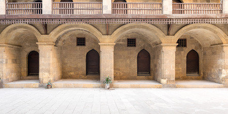surmounted: Facade of the ground floor of caravansary (Wikala) of Bazaraa showing four arches, four wooden doors and small windows of accommodation rooms surmounted by wooden balustrades, Cairo, Egypt
