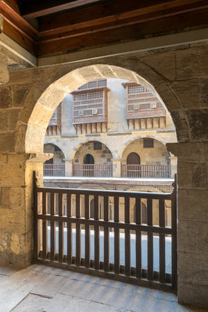 interleaved: Angled view of one arch with interleaved wooden balustrades at the arcade surrounding the courtyard of caravansary (Wikala) of Bazaraa, Medieval Cairo, Egypt