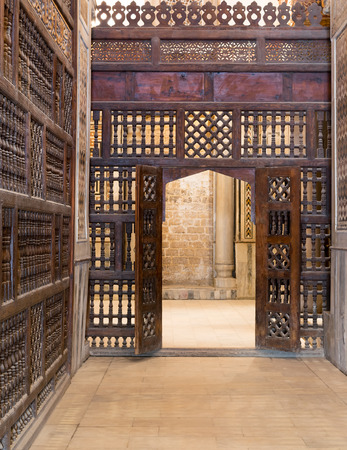 interleaved: Interleaved wooden wall (mashrabiya) with wooden ornate door in Sultan Qalawun mosque, a historic mosque in Old Cairo, Egypt Stock Photo