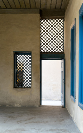 interleaved: Blue vintage wooden window with interleaved wooden grid (mashrabiya) and blue wooden door with plaster yellow wall