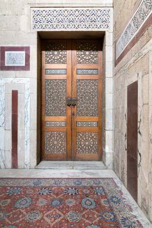 Ancient decorated door (arabesque) and decorated colored marble wall, Old Cairo, Egypt