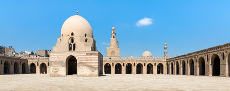 Courtyard of Ibn Tulun Mosque, Cairo, Egypt. View showing the ablution fountain, minaret and minarets of adjoining mosques. The mosque is the largest in the city, and the oldest with its original form