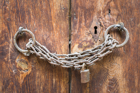 Old rusted padlock, rusted chain, and keyhole on a closed wooden aged grunge double door Stock Photo