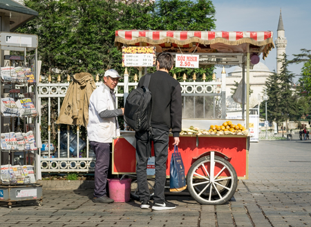 Istanbul, Turkey - April 16, 2017: Tourist buying fast food meal from a traditional Turkish chestnut and corn cart in Sultan Ahmed Square Editorial