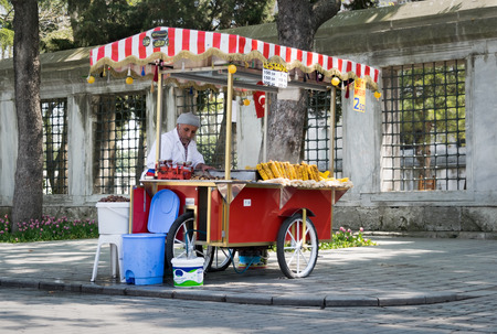 Istanbul, Turkey - April 16, 2017: Old man selling chestnut and corn on traditional Turkish fast food cart in Sultan Ahmed Square Editorial