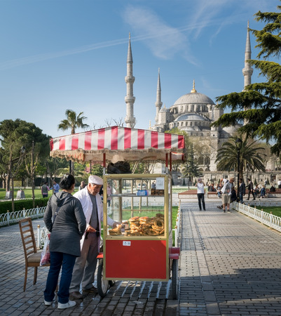 Istanbul, Turkey - April 16, 2017: Tourist buying fast food meal from a traditional Turkish Simit (Bagel) cart in Sultan Ahmed Square Editorial