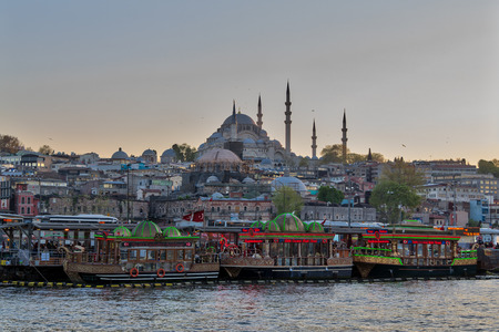 Istanbul, Turkey - April 25, 2017: Traditional fast food bobbing boats serving fish sandwiches at Eminonu district with Rustem Pasha Mosque and Suleymaniye Mosque in the background before sunset