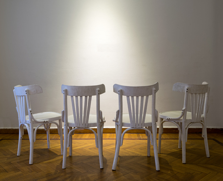 Four white wooden chairs facing spot lighted white wall on wooden parquet floor