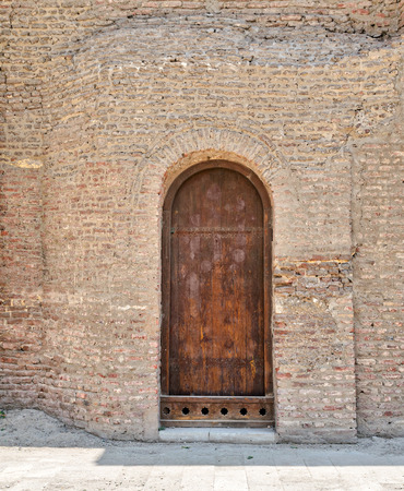 Grunge wooden aged vaulted door on exterior stone bricks wall of Amr Ibn Al-As, Medieval Cairo, Egypt