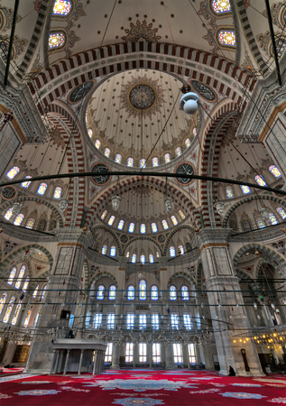 Istanbul, Turkey - April 25, 2017: Interior of Fatih Mosque, a public Ottoman mosque in Fatih district with a huge decorated domes & many colored stained glass windows Editorial