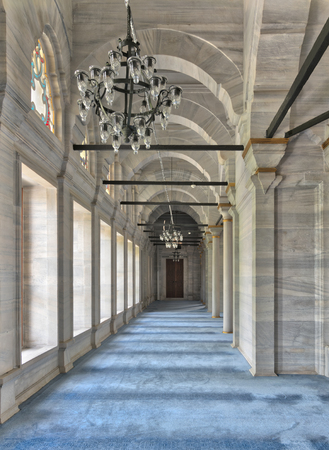 Passage in Nuruosmaniye Mosque, a public Ottoman Baroque style mosque, with columns, arches and floor covered with blue carpet lighted by side windows located in Shemberlitash, Fatih, Istanbul, Turkey Editorial