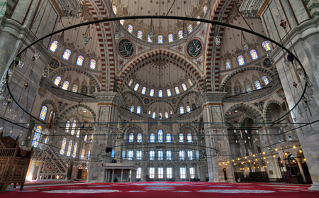 Istanbul: Fatih Mosque, a public Ottoman mosque in the Fatih district with a huge decorated domes & many colored stained glass windows and few people reading Quraan before mid-day (Zuhr) prayers
